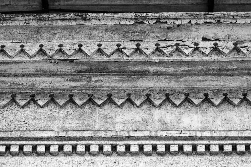 Black and white architectural detail photograph of decorative but decaying woodwork on the eave of an abandoned house in the New Orleans French Quarter.
