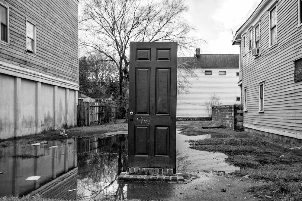 Black and white photograph of a standing front door without a house attached, seen in an empty lot in Charleston, South Carolina.