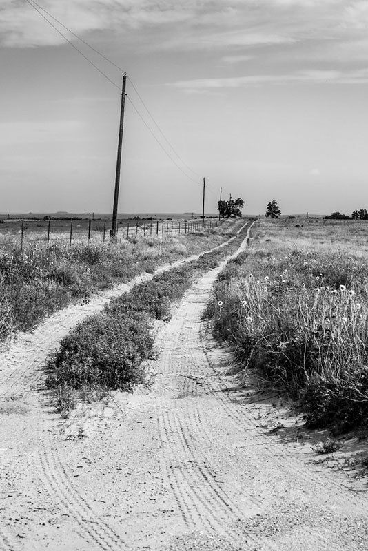 Black and white photograph of a dirt road leading into the flat, wide horizon of the Texas Panhandle.