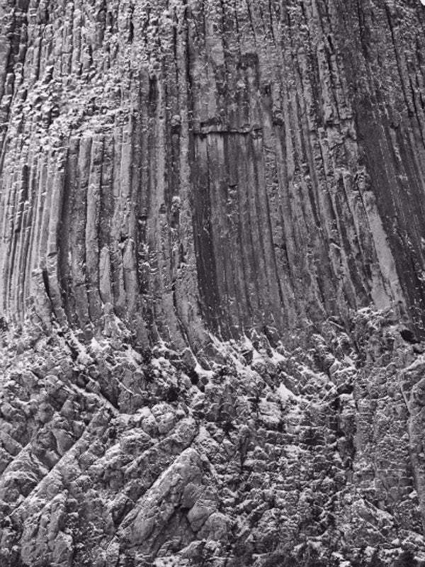 Black and white detail photograph of the face of Devil's Tower, with a light frosting of snow.