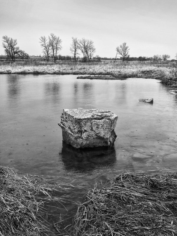 Black and white landscape photograph of a rock in the middle of the Pipestone Creek on the chilly Minnesota prairie in early Spring.