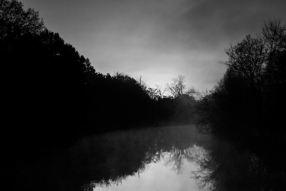 Black and white photograph of Bayou Teche, near Lafayette Louisiana, with the sun rising through the fog.