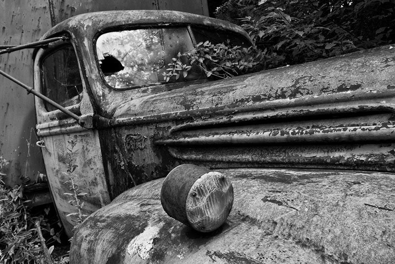 Black and white fine art photograph of a wrecked and abandoned delivery truck. Someone drove this hand-painted antique truck, into a ditch on a winding country road, and never returned to retrieve it. It still sits there rusting away among the tall weeds and grass.
