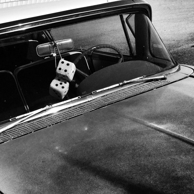 Black and white Instagram photograph of fuzzy dice on the rear view mirror of a restored 1950s automobile.