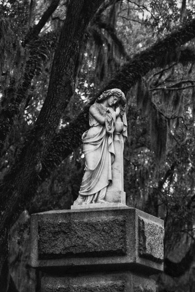 Black and white photograph of the statue on the entrance gate to Savannah's famous, beautiful, and creepy Bonaventure Cemetery.