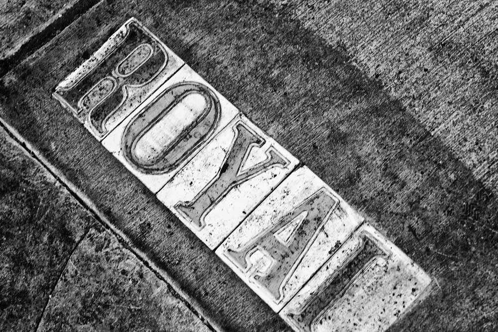 Black and white fine art photograph of dirty Royal street sign letters in a sidewalk in the French Quarter of New Orleans, Louisiana.