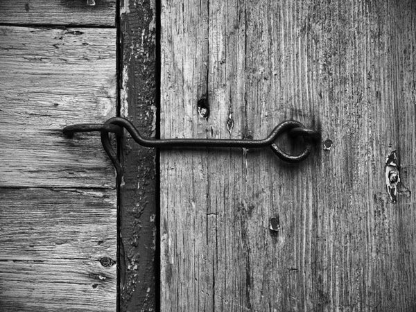 Black and white detail photograph of a door latch on the screen door of an old house.