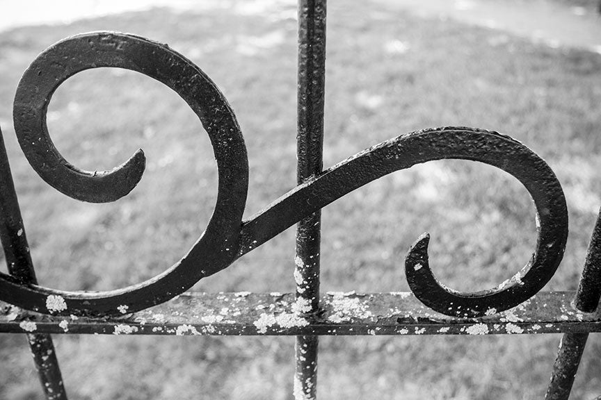 Black and white photograph of iron flourishes on an old fence at the historic antebellum plantation house at Carnton, in Franklin, Tennessee.