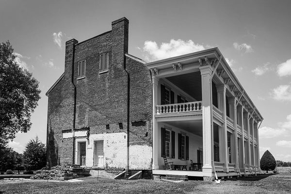Black and white photograph of the historic antebellum plantation house at Carnton, in Franklin, Tennessee. Carnton is a Federal-style plantation house built in 1826. The house and farm was a key site of the American Civil War during the Battle of Franklin in 1864, with the house transformed into a field hospital. Blood stains from surgeries can still be seen in the wood floors of the house, contributing the home's reputation as being haunted.