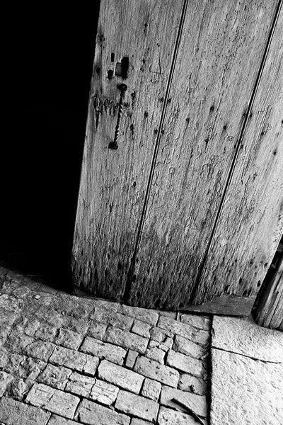 Black and white photograph of the old worm-eaten wooden door and stone floor of the Carnton Plantation smokehouse, an outbuilding that was constructed in 1815.