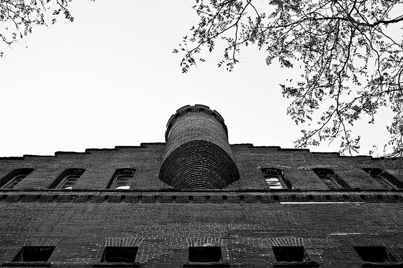 Black and white photograph of University of Wisconsin's Armory and Gymnasium, in Madison, Wisconsin. Better known as the old red gym, the structure was designed in the Romanesque revival style resembling a red brick castle. It was originally used as a combination gymnasium and armory beginning in 1894. It may seem odd to combine a gym with an armory, but it was funded after the Chicago Haymarket Riot in a time of labor unrest, when cities were building militias to put down worker strikes and protests.