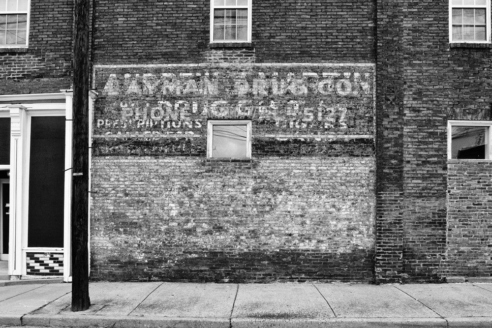 "Black and white photograph of the side of an old pharmacy building in the Chestnut Hill neighborhood of Nashville, with a fading painted sign that reads ""Layman Drug Co."""