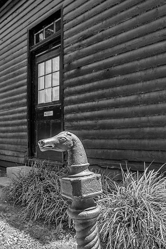 Black and white photograph of a horse head hitching post in the yard at the historic Carter House in Franklin, Tennessee. The house and its property was a site of bloody fighting during the battle of Franklin, and bullet holes can still be seen in shed in the background.