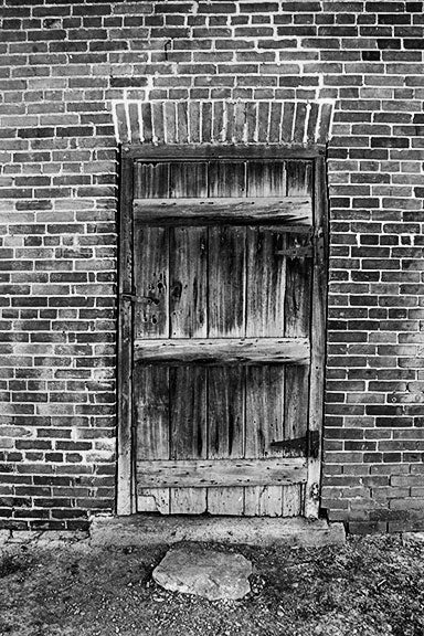 Black and white photograph of a wooden door in an old brick outbuilding on the property of the historic Carter House in Franklin, Tennessee. The house and its property was the site of bloody fighting during the battle of Franklin, and original musket ball holes can still be seen in the house and sheds.