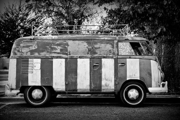 Black and white photograph of a vintage VW van that's been hand-painted top-to-bottom with a giant US flag.