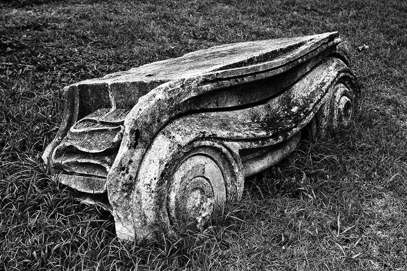 "Black and white photograph of an Ionic Capitol from a Greek Revival column lying in the grass. Removed from the original Tennessee State Capitol building in Nashville during a renovation, these pieces of stone columns have been scattered around Nashville as a reminder of its reputation as ""the Athens of the South."""
