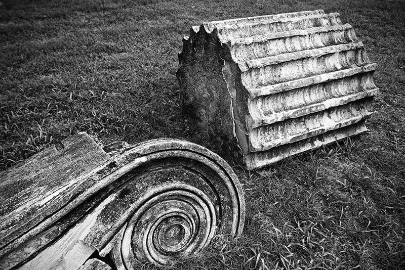 "Black and white photograph of a fallen Greek Revival column lying in the grass. Removed from the original Tennessee State Capitol building in Nashville during a renovation, these pieces of stone columns have been scattered around Nashville as a reminder of its reputation as ""the Athens of the South."""