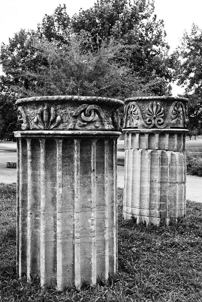 "Black and white photograph of two standing Greek Revival columns in Nashville. Originally part of the Tennessee State Capitol building, these columns were removed during a renovation and have been scattered around Nashville as a reminder of its reputation as ""the Athens of the South."""