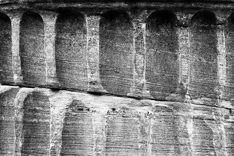 "Black and white detail photograph of a Greek Revival column fragment from the original Tennessee State Capitol building in Nashville, Tennessee. These pieces of stone columns have been scattered around Nashville as a reminder of its reputation as ""the Athens of the South."""
