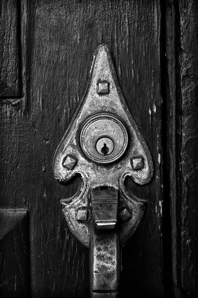 Black and white architectural detail photograph of an old brass door handle on a textured black door.