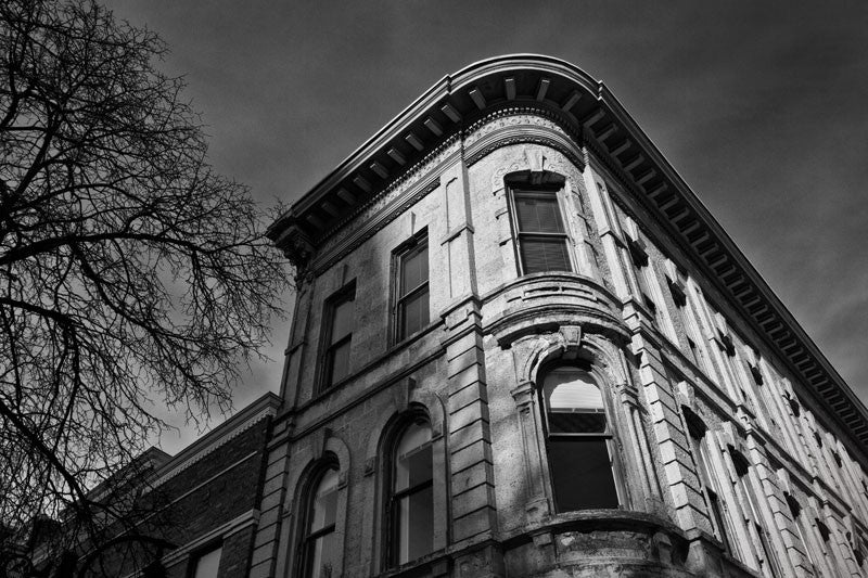 Black and white photograph of a historic building on the corner of the downtown square in Madison, Wisconsin, just catching the low light of the winter sun.