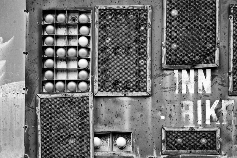 Black and white photograph of a section of an old, fading and dented scoreboard on the outfield of an abandoned baseball field. The ball field has since been plowed under and converted to parkland, and the scoreboard has been scrapped.