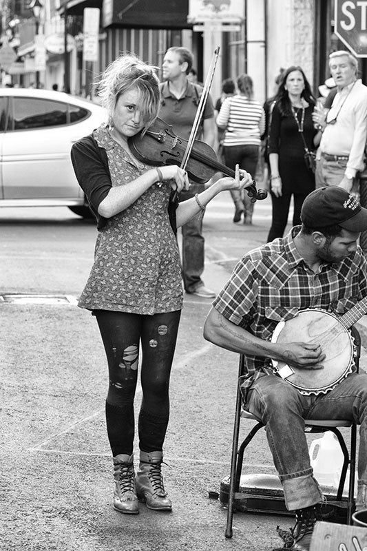 Black and white fine art photograph of a street musician playing a violin with her band in the New Orleans French Quarter.