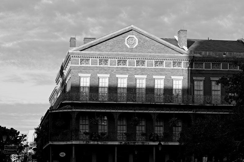 Black and white photograph of the sun setting on historic Jackson Square in the French Quarter of New Orleans. Jackson Square is a National Historic Landmark due to its role in the Louisiana Purchase in 1803.