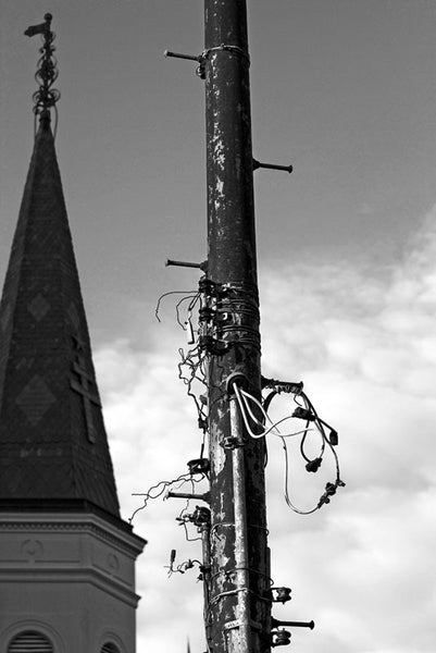 Black and white photograph of an unkempt utility pole in New Orleans' Jackson Square. One of the spires of St. Louis Cathedral is visible on the left.