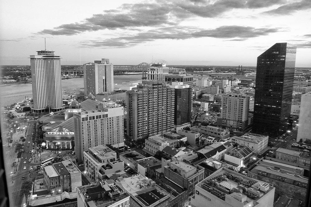 Black and white photograph aerial view of New Orleans business district, Canal Street and the Mississippi River.