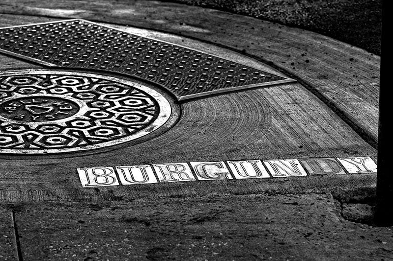 Black and white fine art photograph of the Burgundy street sign letters in the sidewalk beside a manhole cover in the French Quarter of New Orleans, Louisiana.