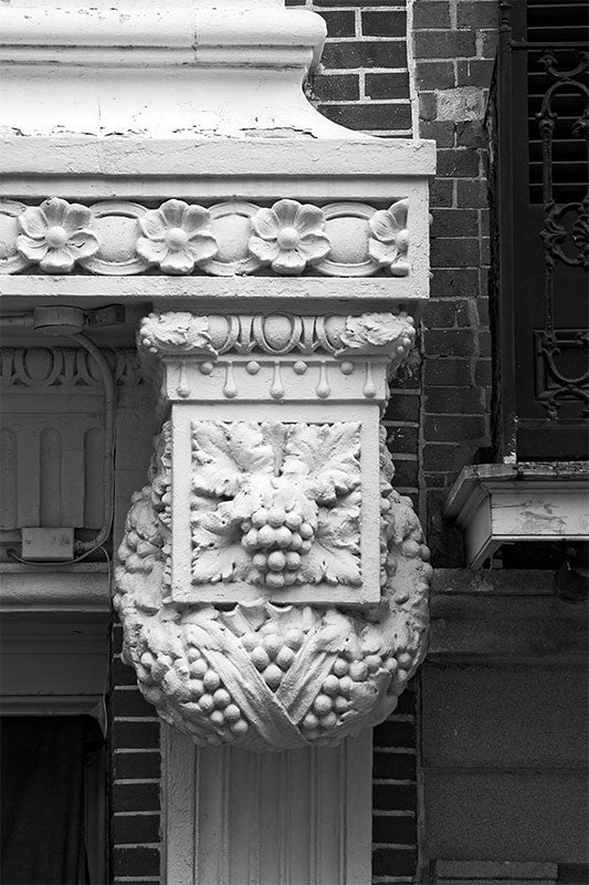 Black and white architectural detail photograph of decorative metalwork with a grape cluster and floral motif in New Orleans.