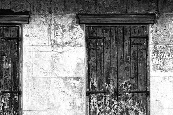 Black and white photograph of a beautifully textured wall with wooden window shutters and fading paint, seen in the New Orleans French Quarter.