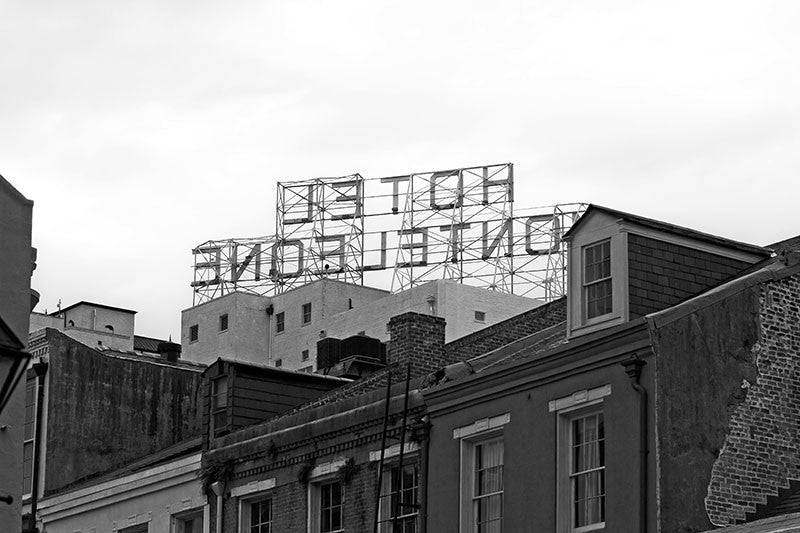 Black and white photograph of rooftop sign of the Hotel Monteleone, seen from behind, in New Orleans' famous French Quarter.