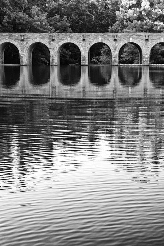 Black and white landscape photograph of the arches of an old stone bridge reflecting in quiet water.