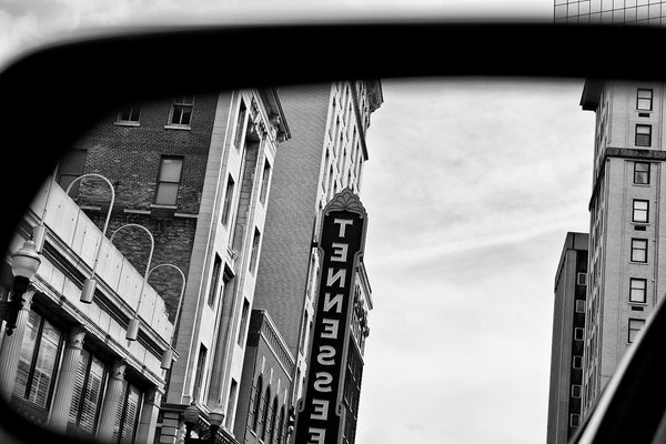 Black and white photograph of the famous Tennessee Theatre sign in Knoxville, reflected in a car's rearview mirror.