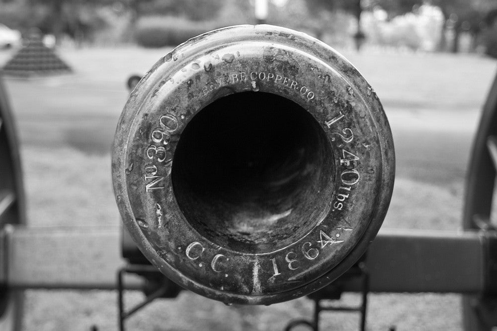 "Black and white photograph of the muzzle of a civil war cannon at Stones River National Military Cemetery in Murfreesboro, Tennessee. The engraving reads ""No. 390. Revere Copper Co. 1240 lbs. C.C. 1864."""