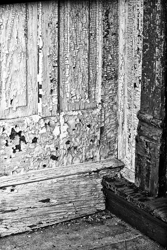 Black and white photograph of peeling paint on an abandoned building in a small town that was once adapted by one of the many groups in the late 1800s who sought to create a perfect society under utopian ideals.