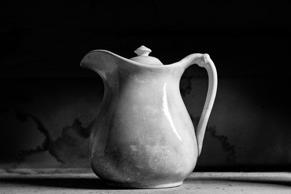 Black and white photograph of a simple and beautiful antique white pitcher with a gorgeous craquelure surface within the glaze