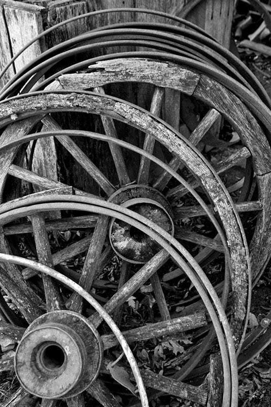 Black and white photograph of a stack of broken old wooden wagon wheels and metal rims.