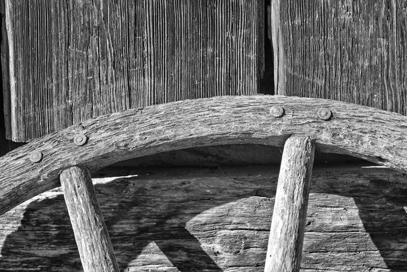 Black and white detail photograph of an old wooden wagon wheel leaning against a textured wooden wall.