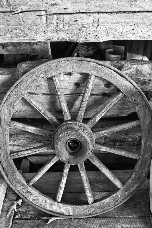 Black and white photograph of an antique spoked wagon wheel found inside a wooden barn.