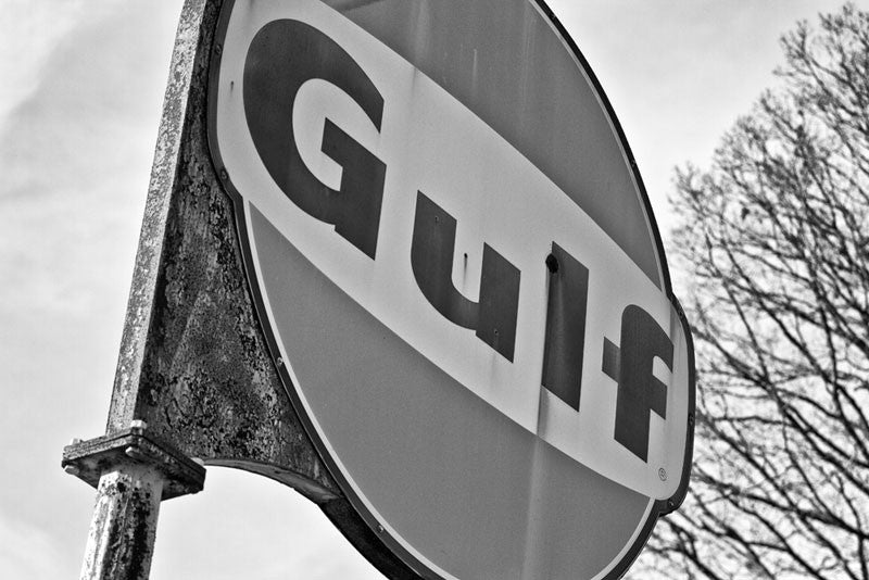 Black and white photograph of a rusty and fading Gulf gas station sign that still stands outside a long-vacated and abandoned service station on a rural highway in the southern US.