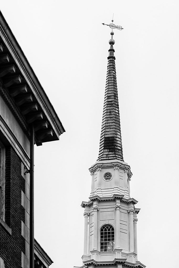 Black and white architectural photograph of a historic church steeple towering above the city