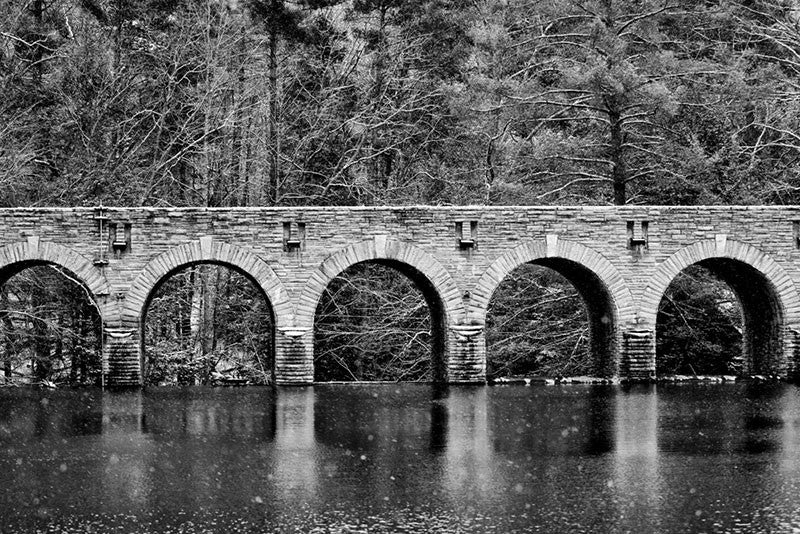 Black and white landscape photograph of an old stone bridge reflecting in a cold river in winter, with snowflakes flying.