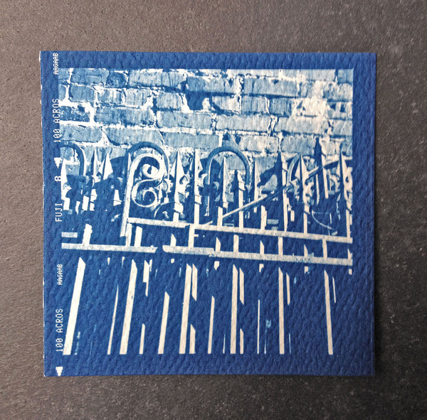 This is a unique, small, one-of-a-kind handmade cyanotype print of a many sets of antique ironwork fences stacked against a brick wall. This was contact printed from a 2-1/4 inch black and white film negative on textured ivory watercolor paper, handmade and printed by the artist.