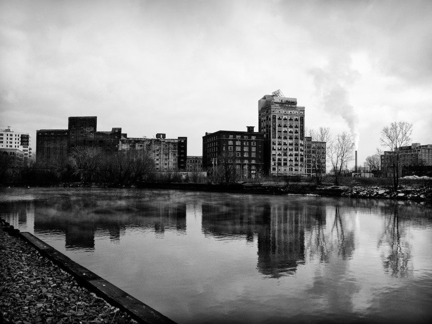 Black and white photograph of industrial buildings reflecting in a river in Milwaukee.