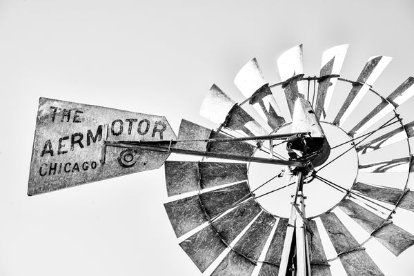 "Black and white photograph of an old windmill in the American southwest that says ""The Aermotor Co. Chicago""."