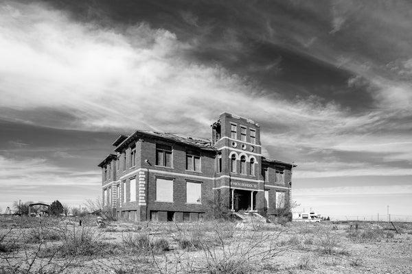 Black and white photograph of a desert landscape featuring an abandoned and derelict high school building.