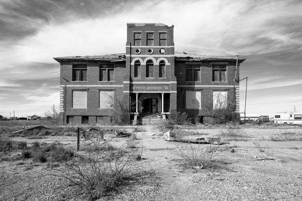 Black and white photograph of an abandoned and derelict high school building in a small town in the desert of the Western U.S. The sign over the entrance is dated 1912.